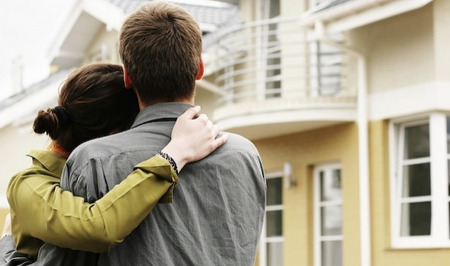 Couple embracing each other in front of a house